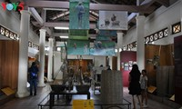 Museum displays farming tools by Thanh Toan tile-roofed bridge