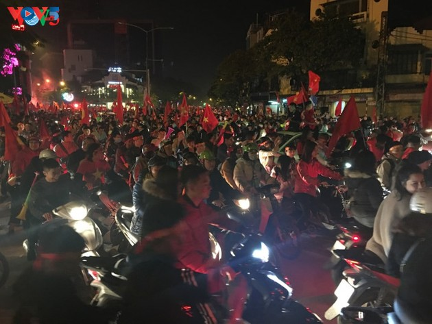 Hanoi streets covered in red flags, cheer football squad winning trophy