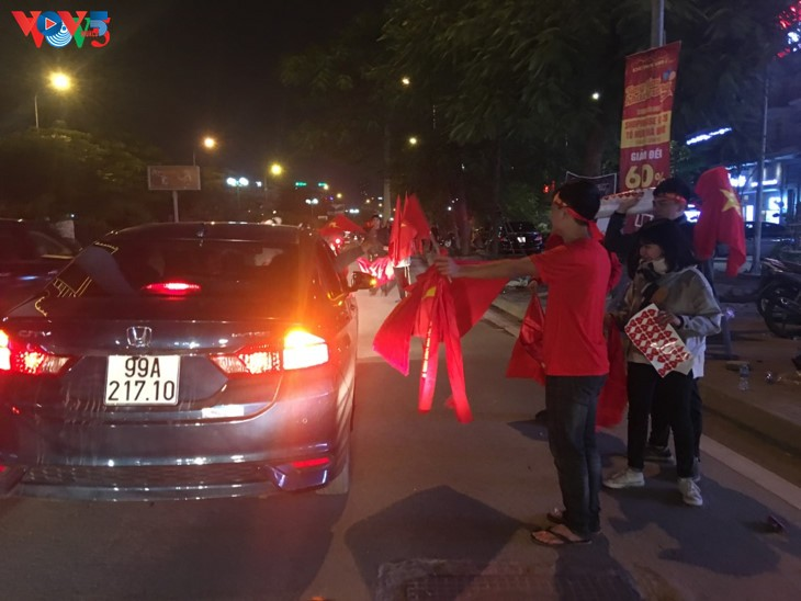 Hanoi streets covered in red flags, cheer football squad winning trophy - ảnh 1