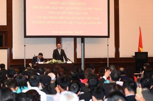 PM Nguyen Xuan Phuc melakukan pertemuan dengan para pejabat dan staf Kedutaan Besar dan wakil dari komunitas orang Vietnam di Jerman - ảnh 1