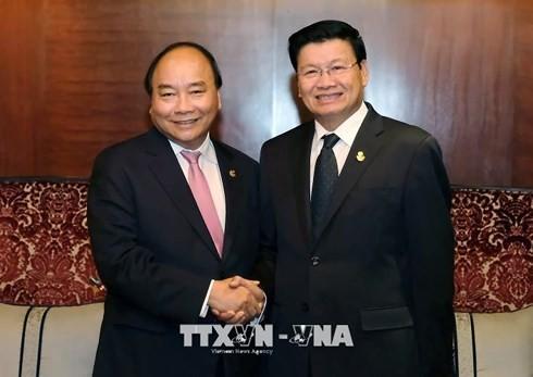 PM Nguyen Xuan Phuc melakukan pembicaraan dengan PM Thailand, Prayuth Chan-ocha dan PM Laos, Thongloun Sisoulith - ảnh 1