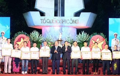 阮春福在河内山西烈士墓园向烈士家属颁发祖国记功证书并上香 - ảnh 2